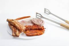 Grillat kött i platta med tång på vit bakgrund royaltyfria bilder