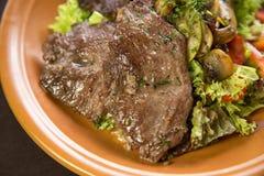 Grillat kött: kalvkött som garneras med tomater, champinjoner och grönsallat Arkivfoto