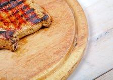 Grillat kött på träbräde arkivfoton