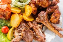 Grillat kött, stöd, grillad laxfisk, potatisar, örter och tomat på den vita plattan och den vita trätabellen Slut upp med selekti royaltyfri bild