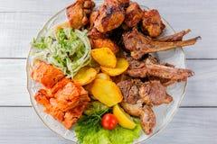 Grillat kött, stöd, grillad laxfisk, potatisar, örter och tomat på den vita plattan och den vita trätabellen Top beskådar royaltyfria foton