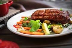 Grillat kasta nötköttbiff med grönsaker på plattan royaltyfri bild