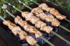 Grillaufsteckspindeln mit Fleisch auf dem Messingarbeiter Huhn shish kebab Stockfotografie