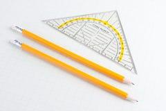 Grille de tabulation et crayons de mathématiques sur le papier carré Photos stock