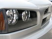Grille and lights of new silver car. Head lights and grille of shiny new silver car royalty free stock image