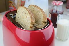 Grille-pain rouge avec du pain du blé entier deux dans les poches images stock