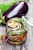 Grilled切了茄子用在玻璃瓶子的辣椒在土气桌上 免版税库存图片
