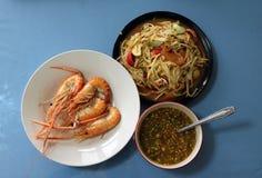 Grilled烹调了在白色盘的虾用在碗和番木瓜沙拉的调味汁在黑盘 库存图片