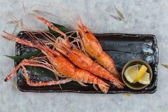 Grilled虾巨型老虎典当顶视图与盐的服务用在黑石板材的切的柠檬在washi日文报纸 库存照片