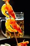 Grilled зажарило креветок на деревянных протыкальниках с специями На предпосылке кружки с пивом, сковорода чугуна с креветками ба Стоковая Фотография RF