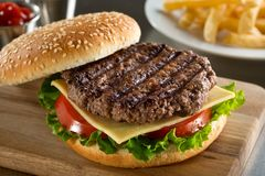 Grilled Angus Burger. A delicious grilled Angus burger with cheese, lettuce, and tomato on a sesame seed bun royalty free stock photo