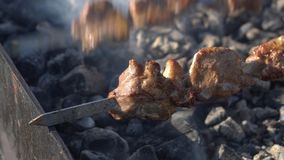 Grilled appetizing pork shish kebab cooking on charcoal grill with smoke stock video footage