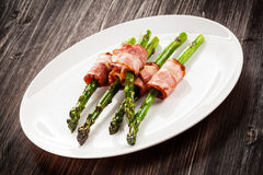 Grilled asparagus with beacon. Grilled aparagus and beacon on white plate Royalty Free Stock Photography