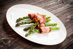 Grilled asparagus with beacon. Grilled aparagus and beacon on white plate Royalty Free Stock Image