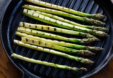 Grilled asparagus. Grilled green asparagus on a cast iron grillpan royalty free stock photo