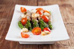 Grilled asparagus with prosciutto, moyyarella and cherrz tomatoe Royalty Free Stock Photos
