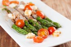 Grilled asparagus with prosciutto, mozzarella and cherry tomatoe Stock Image