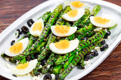 Grilled asparagus salad with feta cheese, olives and eggs Stock Image