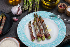 Grilled asparagus wrapped in pancetta or bacon, italian cousine. Serwed on wooden table Royalty Free Stock Images