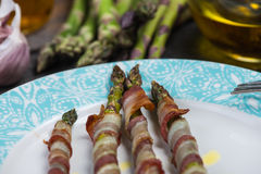 Grilled asparagus wrapped in pancetta or bacon, italian cousine. Serwed on wooden table Stock Images