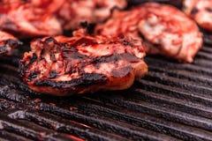 Grilled a assaisonné le poulet que les cuisses font cuire sur un gril de barbecue de fonte avec de la sauce fraîche à BBQ Image libre de droits