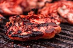 Grilled a assaisonné le poulet que les cuisses font cuire sur un gril de barbecue de fonte avec de la sauce fraîche à BBQ Images stock