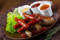 Grilled assorted sausages with sauces Royalty Free Stock Photography