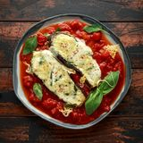 Grilled aubergine, eggplant topped with parmesan cheese crust on crashed tomatoes. Vegetarian pizza version stock photos
