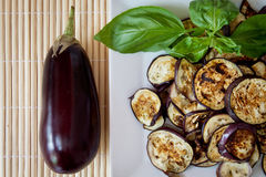 Grilled aubergines with basil, detail. Platter of grilled aubergines with basil and a whole aubergine on the side Royalty Free Stock Photography