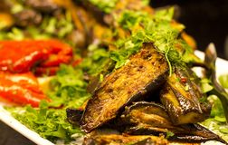 Grilled aubergines with tomatoes and greens. Selective focus royalty free stock photo