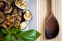 Grilled aubergines with wooden spoon, detail. Platter of grilled aubergines with basil and wooden spoon on the side Royalty Free Stock Photography