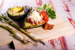 Grilled Avocado with cheese and salsa. Fresh Grilled avocado halves with Salsa Stock Photos
