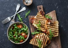 Grilled bacon, mozzarella sandwiches on wooden cutting boards and arugula, cherry tomato salad on dark background, top view.Delici. Ous breakfast or snack, flat Royalty Free Stock Images