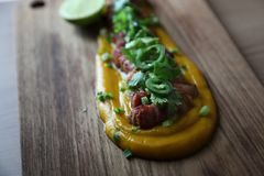 Grilled bacon with pumpkin sauce on wooden table. In close up stock photos