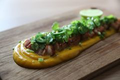 Grilled bacon with pumpkin sauce on wooden table. In close up stock image