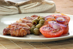Grilled bacon rolls and olive Stock Images