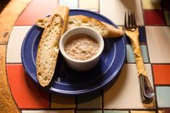 Grilled baguette with fish pate. Appetizer in a blue plate, colorful tiled table.  Stock Photos