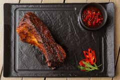 Grilled and barbecue hot pork ribs with hot chilli pepper and hot sauce on black stone background. Isolated. Dish for royalty free stock photography
