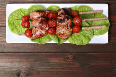 Grilled barbecue kebab chicken legs and tomatoes on skewers Royalty Free Stock Images