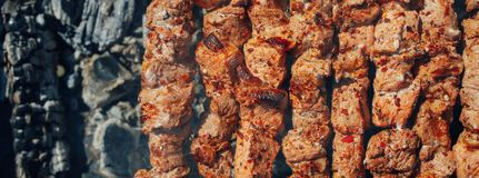 Grilled barbecue meat on skewers and charcoals. Top view Stock Photos