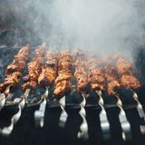 Grilled barbecue meat on skewers with smoke. Closeup view Royalty Free Stock Photos