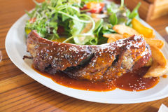 Grilled barbecue pork ribs. With french fries and fresh vegetables on white plate Stock Photography