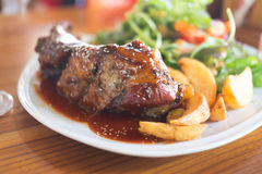 Grilled barbecue pork ribs with french fries. On white dish Royalty Free Stock Images