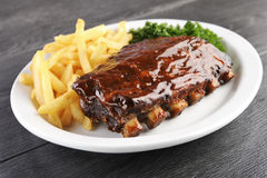 Grilled barbecue ribs. Grilled juicy barbecue pork ribs in a white plate with fries and parsley royalty free stock photography