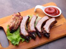 Grilled barbecued ribs with lettuce leaves, hot chili pepper and sauce on wooden cutting board. Stock Photography