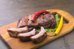Grilled barbecued ribs with lettuce leaves, hot chili pepper and sauce on wooden cutting board. Stock Photo