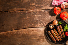 Grilled barbecued sausage with mushrooms. Grilled barbecued sausage with portobello mushrooms and fresh tomato on an old rustic wooden with cracks viewed from royalty free stock photography