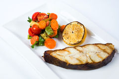 Grilled barramundi steak with lemon and vegetables Stock Photo