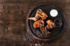 Grilled BBQ chicken. Meat wings served on round wood chopping board with two sauces and salt over dark wooden background. Top view with copy space royalty free stock images