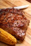 A grilled BBQ ribeye steak. With corn and a knife stock image